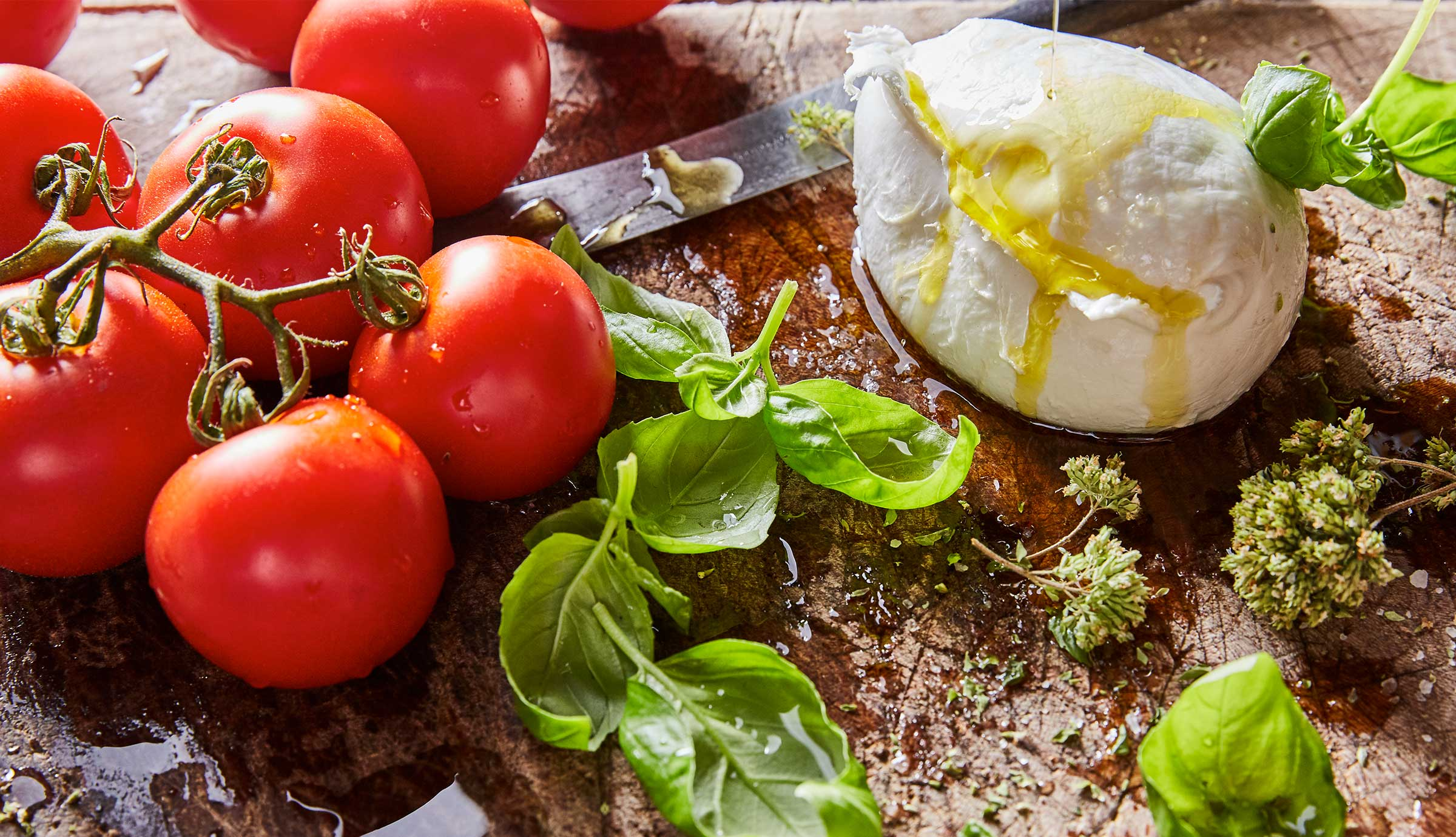 Tomatoes, mozzarella cheese, basil and oregano sit on a wood surface