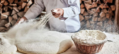 Flour being sprinkled on dough